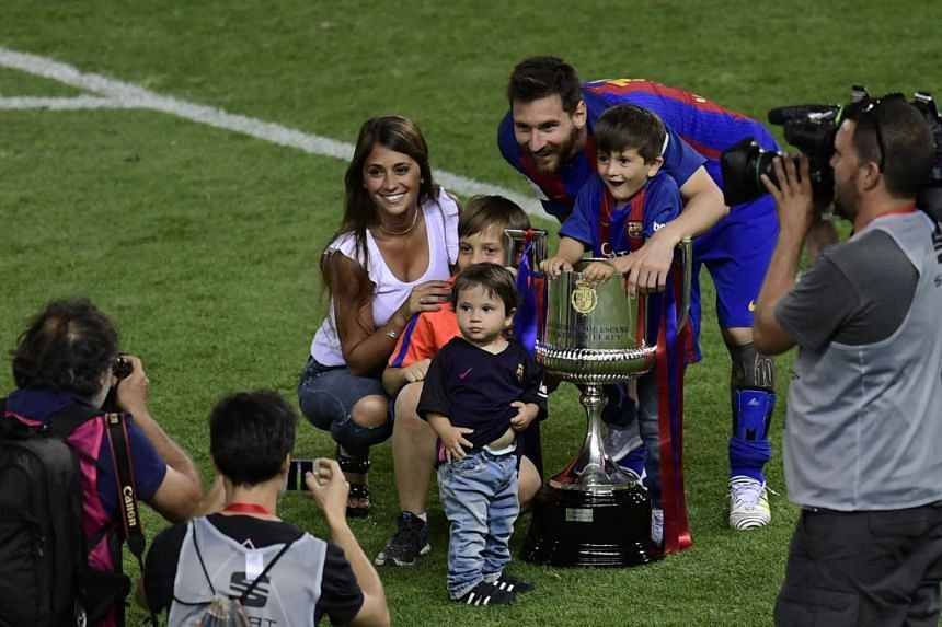 Barcelona's forward Lionel Messi, his wife Antonella Roccuzzo and sons pose with the trophy at the end of the Spanish Copa del Rey (King's Cup) final football match FC Barcelona vs Deportivo Alaves at the Vicente Calderon stadium in Madrid on May 27,