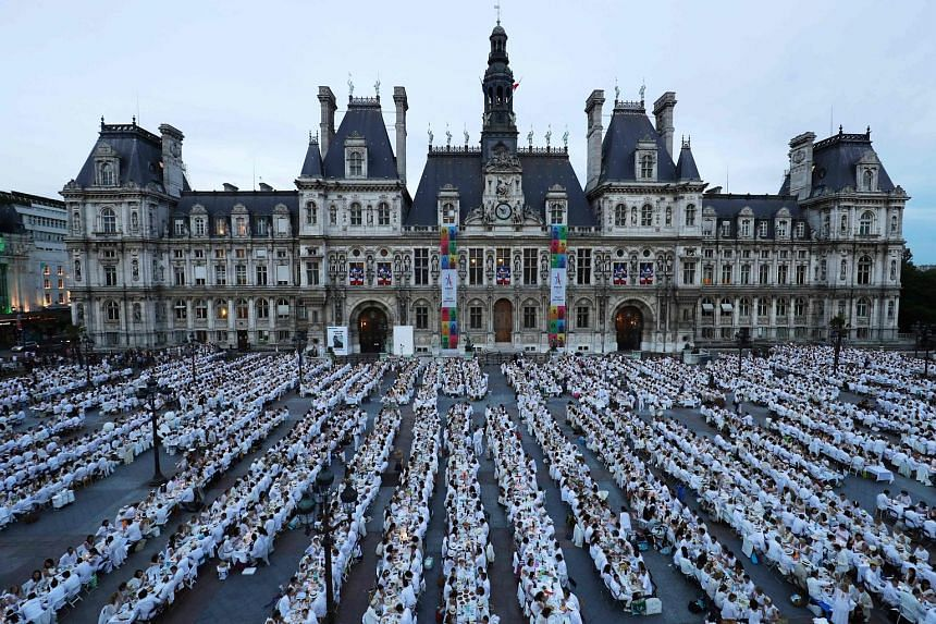 Chic revellers dressed entirely in white taking part in Le Diner en Blanc (Dinner in White) in front of the City Hall in Paris on Thursday. Now into its 29th edition, the annual event draws thousands of guests to each host city around the world, wher