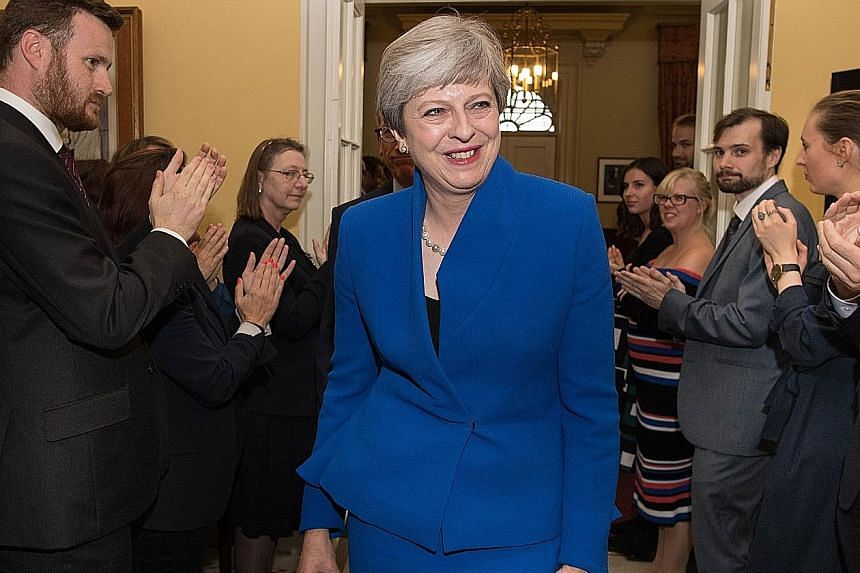 British Prime Minister Theresa May and her husband Philip receiving applause from staff at 10 Downing Street after her audience with Queen Elizabeth II at Buckingham Palace yesterday.