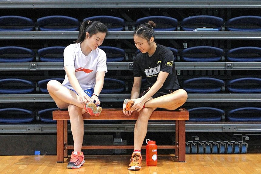 Fleet-footed Yeo Jia Min (right) comparing the sole of her shoes with assistant national singles coach Fu Mingtian during a training session at OCBC Arena yesterday. Her speed is one of her biggest assets.