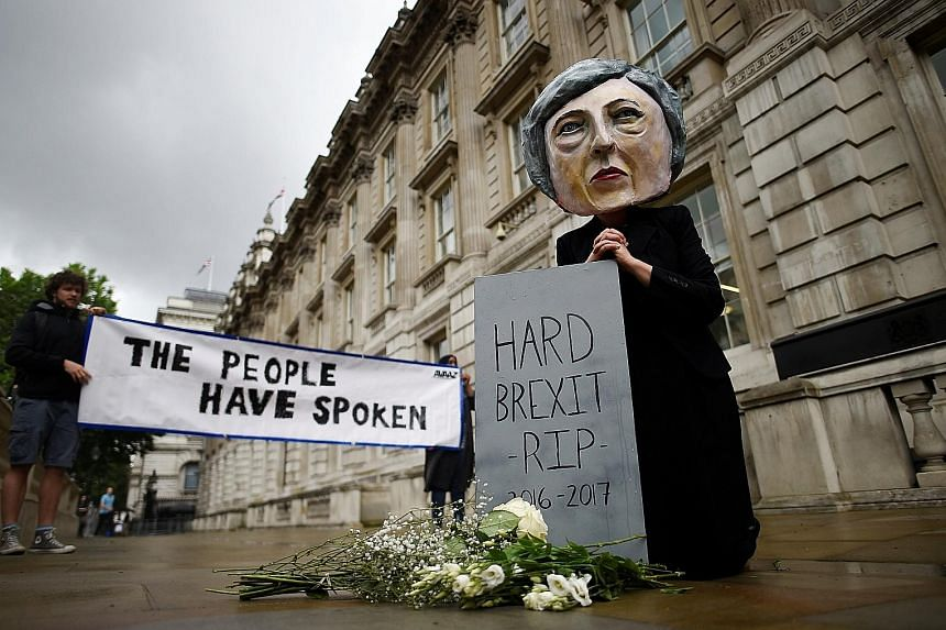 """A demonstrator wearing a Theresa May mask protesting against a """"hard Brexit"""" in London yesterday, following the shock results of the British general election."""