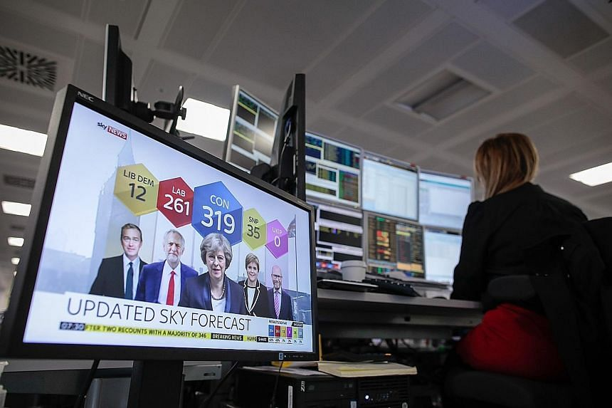 A broker in London monitoring financial data yesterday as results of the UK general election were telecast live.