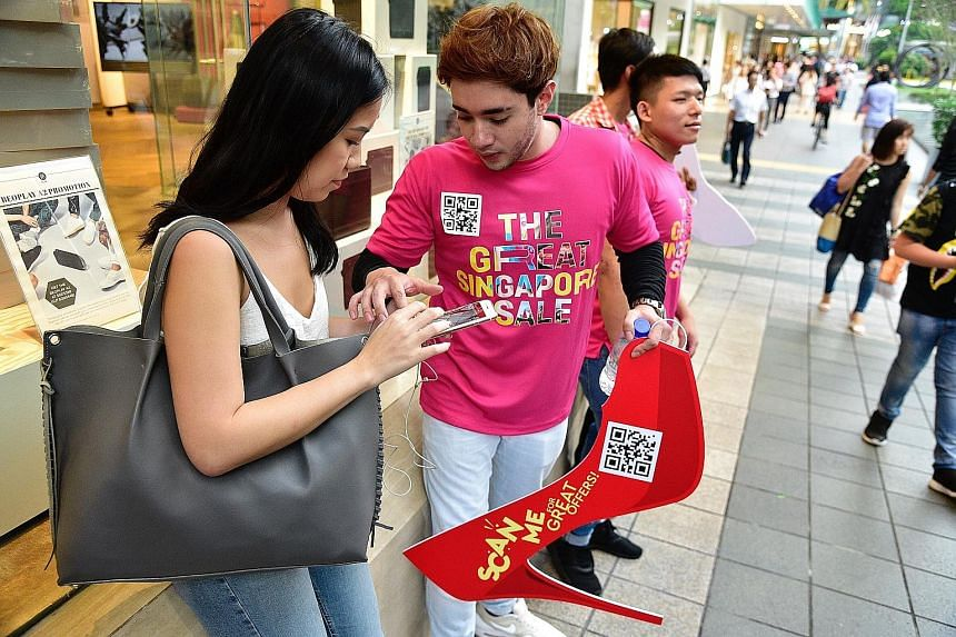Shopper Andrea Lim, 23, learning how to use the GoSpree mobile app that was launched yesterday in conjunction with the start of the Great Singapore Sale. The app, which offers eCoupons from participating retailers, food and beverage operators, hotels