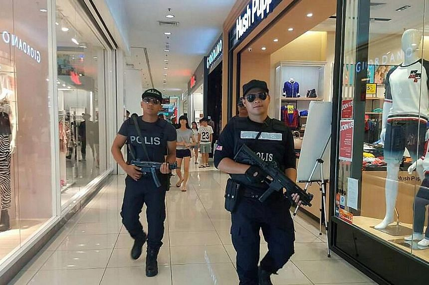 Johor police officers on patrol at a shopping centre. Security has also been stepped up at public places such as bus and train stations.