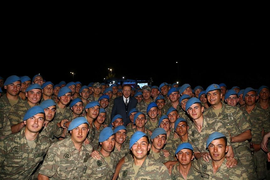 Turkish President Recep Tayyip Erdogan with commandos after an iftar - the breaking of the daily fast during Ramadan - in Kayseri, Turkey, on Thursday. Mr Erdogan rapidly approved a Bill to deploy troops to Qatar after it was pushed through Parliamen