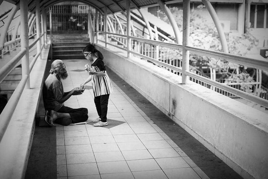 A little girl giving some donation to a beggar on the bridge in Malaysia.