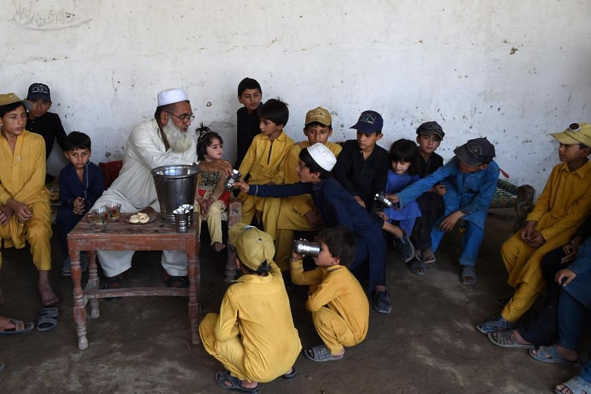 Pakistani father Gulzar Khan (centre), 57, who has 36 children from his three wives, serves drinking water to his children, on May 20, 2017.