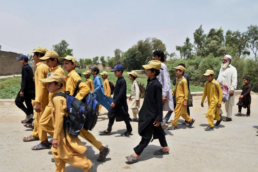 Pakistani father Gulzar Khan (right), walks with his children as they return home after school in the north-western town of Bannu, on May 20, 2017.