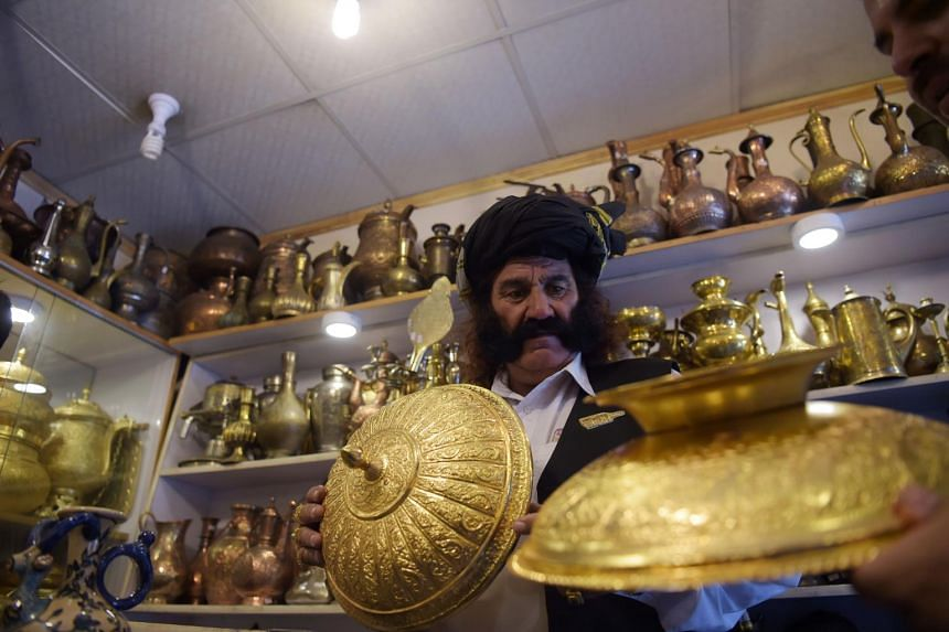 Pakistani man Mastan Khan Wazir, looks at gold pots at a shop in Islamabad, on May 19, 2017.