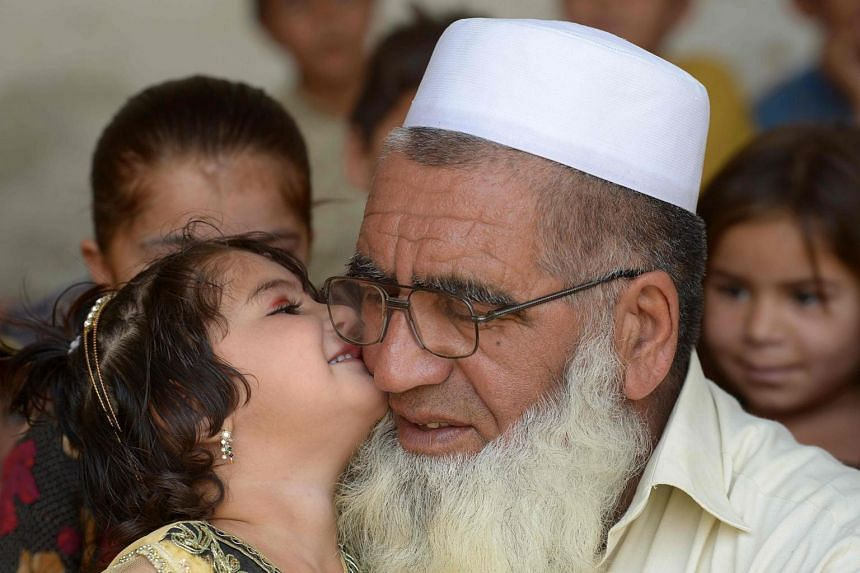 Pakistani father Gulzar Khan receives a kiss from one of his daughters, on May 20, 2017.