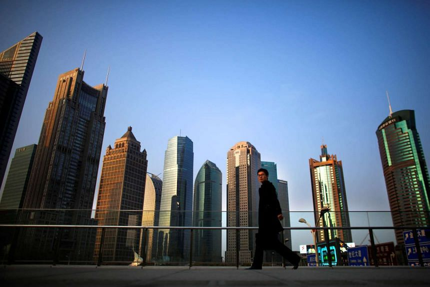 A man walks past the financial district of Pudong in Shanghai.