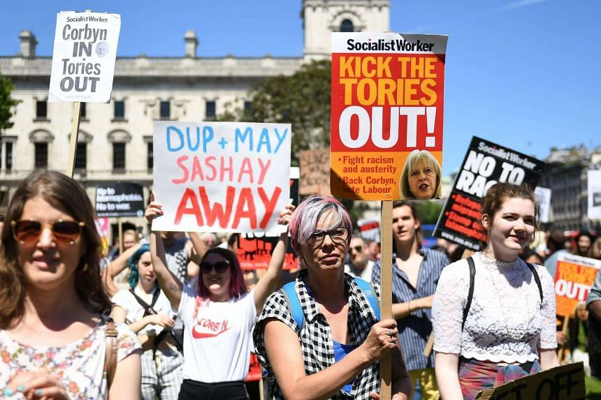 Protesters demonstrate against British Prime Minister Theresa May on Parliament Square in London on June 10, 2017.