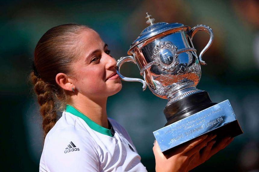 Latvia's Jelena Ostapenko celebrates with her French Open trophy after beating Romania's Simona Halep.