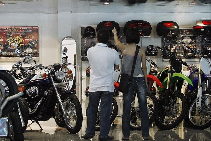 Customers at Mah Motors' motorcycle showroom. FWD's motorcycle insurance recognises safe riders by providing an option to retain and pay the same premium for two years, and a lifetime 20 per cent no claim discount guarantee as long as they are insure