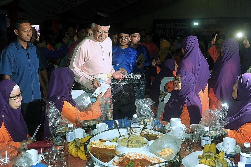 Malaysian Prime Minister Najib Razak attending a breaking of fast programme with settlers at Felda Bukit Sayong in Johor yesterday.