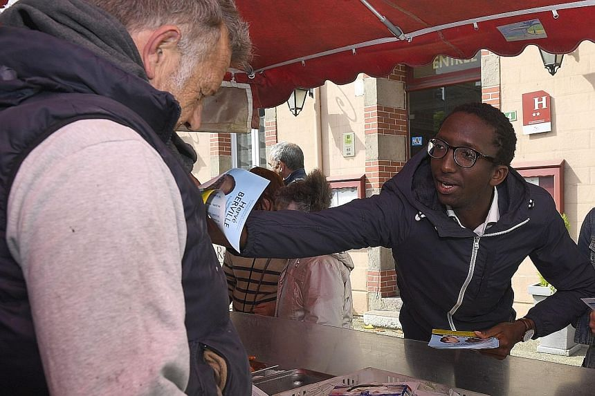 Mr Herve Berville distributing his manifesto in the market of Pleneuf-Val-Andrelast Tuesday. Just 27, he was snapped up last month by President Emmanuel Macron's political movement, La Republique en Marche, to run for a seat in Parliament. Mr Bervill