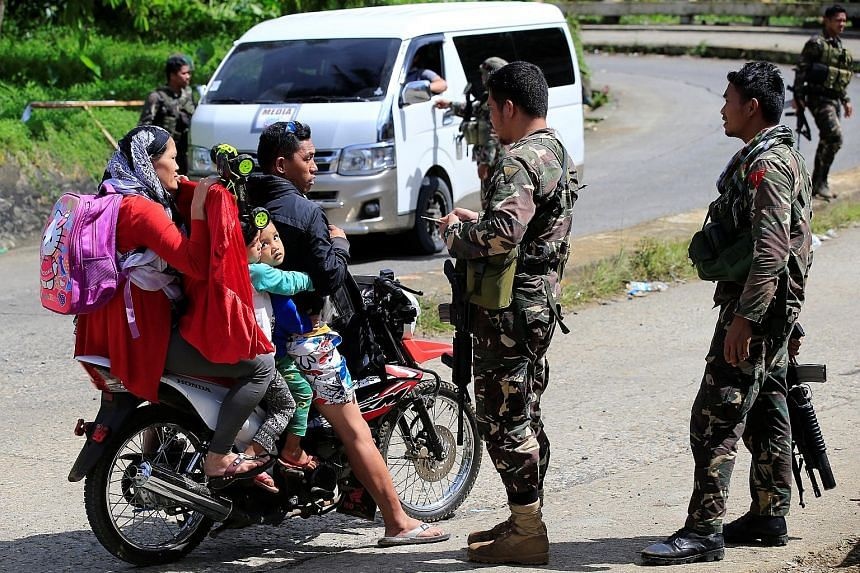 Philippine National Police Special Action Force personnel man a checkpoint in Marawi city as government troops continue their assault against the Maute group. Romato Maute, or Farhana (far left) was arrested on Friday, days after her husband, Cayamor