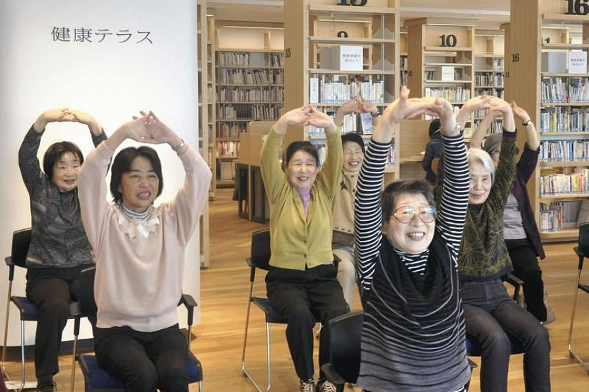 Exercising next to bookshelves filled with health-related books at the Yamato City Library in Kanagawa Prefecture.