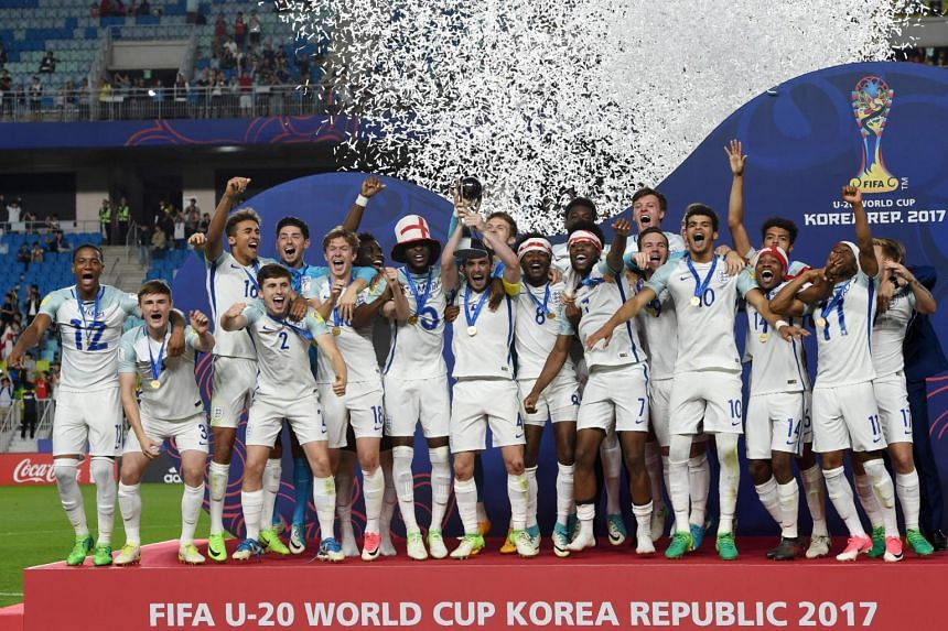 England's players celebrate with the trophy during the awards ceremony after winning the Under-20 World Cup final football match against Venezuela in Suwon on June 11, 2017.