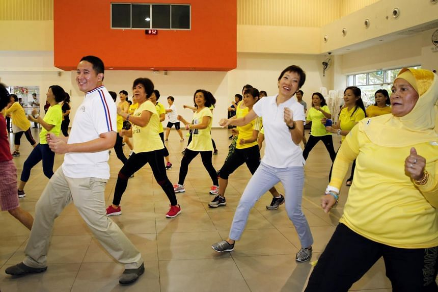 Ms Grace Fu (centre) and Amrin Amin (left), joining the residents in their morning exercises at the Woodlands Galaxy CC on June 11, 2017.