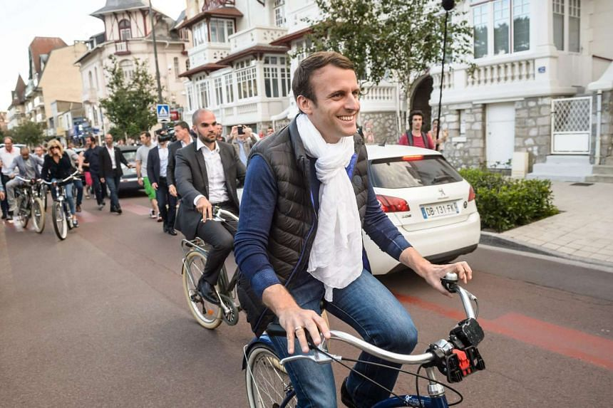 French President Emmanuel Macron leaves home on a bicycle the day before the first round of the French legislatives elections in Le Touquet on June 10, 2016.
