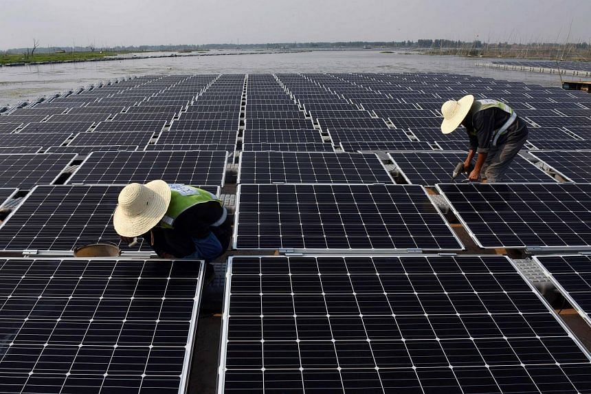 Workers at the world's largest floating solar power plant in Huainan, China on June 7, 2017.