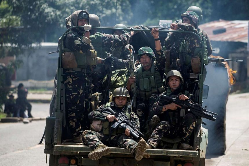 Soldiers aboard their vehicles maneouver through a street in Marawi, in southern island of Mindanao on June 10, 2017.