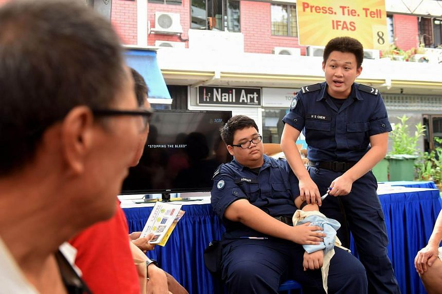 SCDF lance corporal Chew Huan Sheng (right) explaining to Kolam Ayer residents how to dress a wound in an emergency.