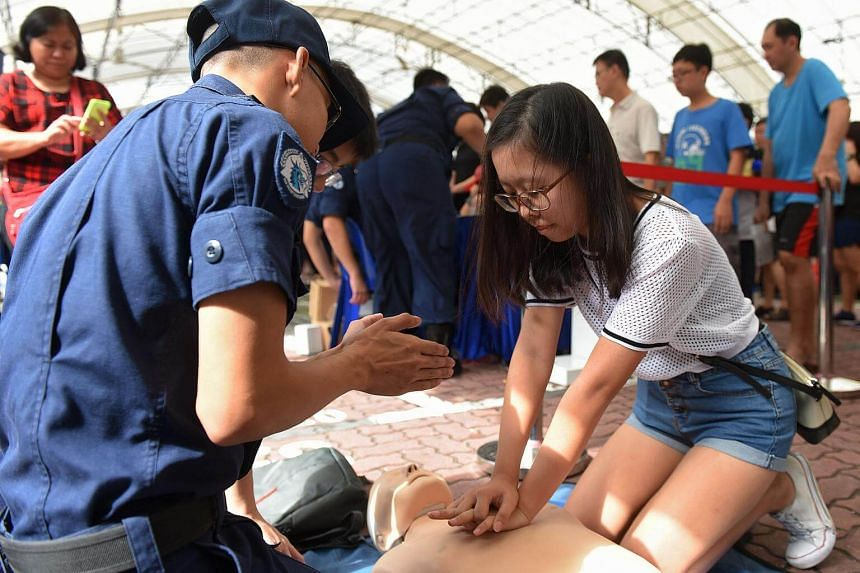Janice Tian, 16, attempts the proper technique of cardiopulmonary resuscitation (CPR) on a mannequin.