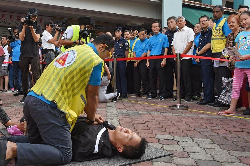 A Community Emergency Response Team (CERT) member simulates a cardiopulmonary resuscitation (CPR) as Minister for Communications and Information and Minister-in-charge of Muslim Affairs Yaacob Ibrahim (in white) watches on.