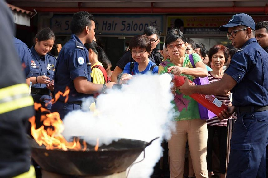 Teo Siew Bee, 56, a teaching assistant and Kolam Ayer resident, tries her hand at using a fire extinguisher under the supervision of SCDF personnel.