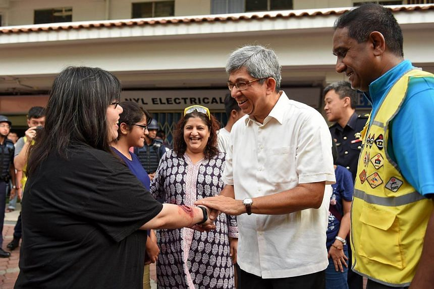 Minister for Communications and Information and Minister-in-charge of Muslim Affairs Yaacob Ibrahim chats with Kolam Ayer resident Frances Lee, who was one of the participants in the terror simulation.