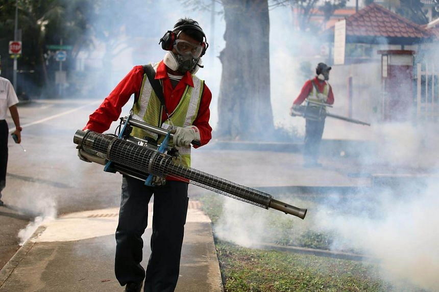 Pest control and National Environment Agency officers fogging an area in Singapore on March 30, 2017.