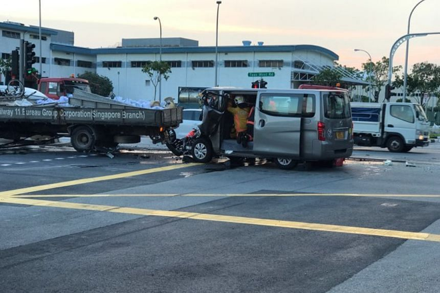 Singapore Civil Defence Force officers rescuing the trapped van driver.