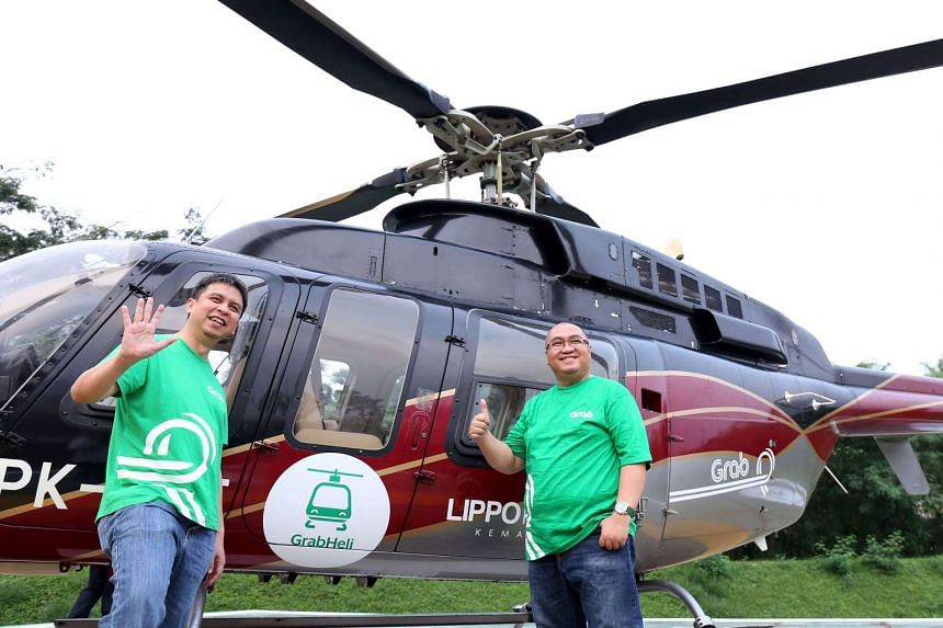 Ridzki Kramadibrata (left), managing director of online ride-hailing firm Grab Indonesia, and Mediko Azwar (right), the company's marketing director, posing prior to taking a helicopter taxi by Grab Indonesia in Jakarta on June 12, 2017.