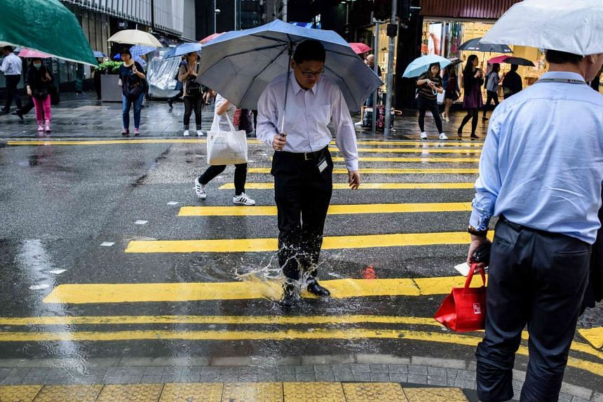 A pedestrian steps into a puddle while crossing a road as it rains in Hong Kong on May 24, 2017.