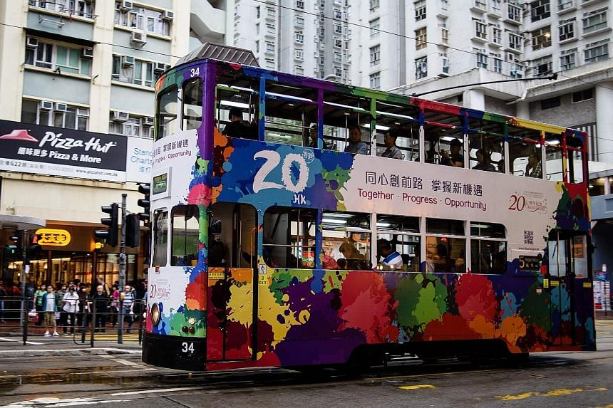 "A tram with a design commemorating the 20th anniversary of Hong Kong's handover to China by Britain. Analysts say the city's unique ""one country, two systems"" framework, with its high degree of autonomy, would give it an advantage over its Chinese ri"