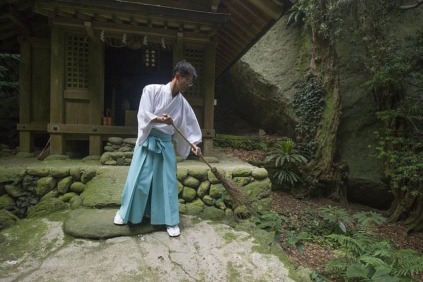 A Shinto priest sweeping at an ancient shrine in Okinoshima, an island in Fukuoka prefecture, on Friday. Okinoshima, which is located between Japan and Korea, will be officially designated as a Unesco World Heritage Site next month, as it is one of t