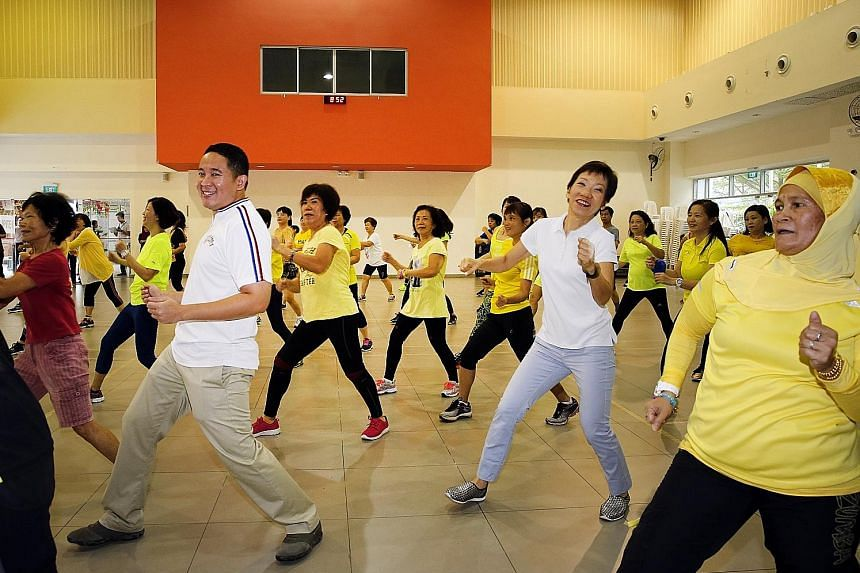 Ms Grace Fu (in white top) joining residents in morning exercises at the Woodlands Galaxy Community Club. With her is Mr Amrin Amin, grassroots adviser and MP for the area.