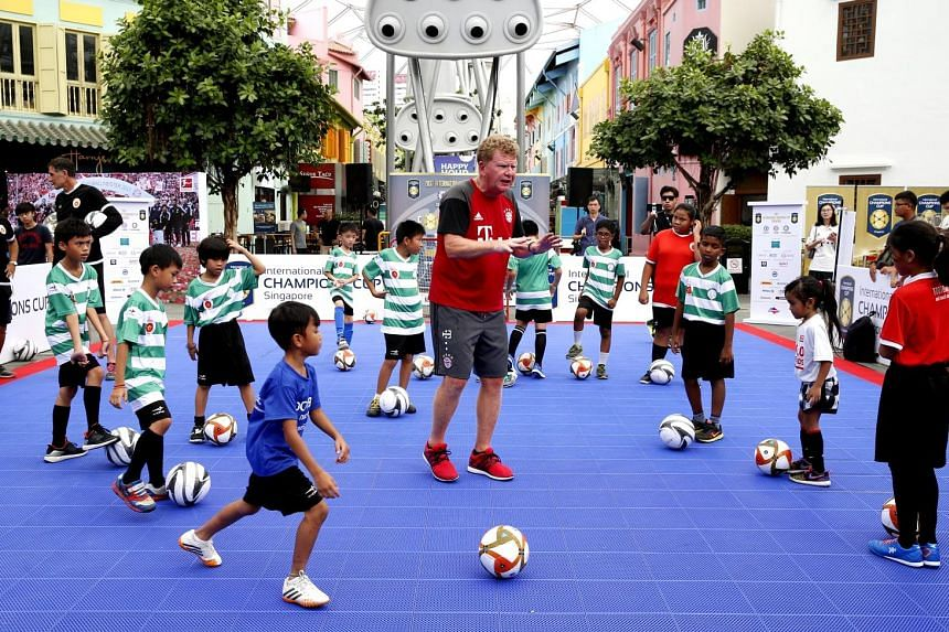 Bayern youth coach Thomas Dollner showing children the basics of dribbling, shooting and passing at a free public football clinic yesterday.
