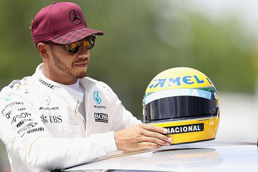 Lewis Hamilton with the replica of a helmet belonging to the late F1 world champion Ayrton Senna, whose record of 65 pole positions he equalled in Montreal for the Canadian Grand Prix.