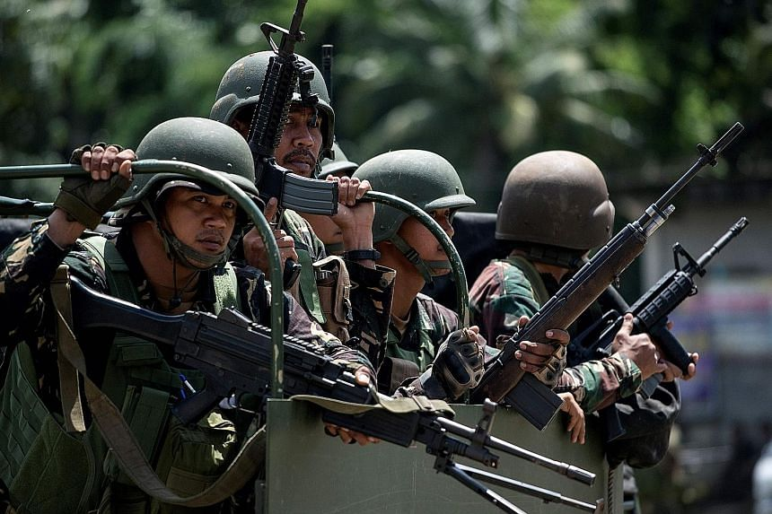Soldiers aboard their vehicles manoeuvring through a street in Marawi, in Mindanao, on Saturday. Philippine troops are struggling to retake the city from the Maute Group, also known as ISIS-Lanao, an ISIS-affiliated terrorist organisation.