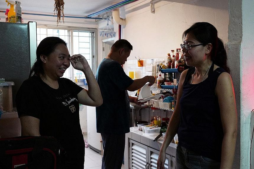 Ms Tang Zhi Ling (far left) and Ms Vivian Pan at the former's flat in Henderson Road. In the background is Mr Ricky Ng, 47, who belongs to Ms Pan's group of volunteers.