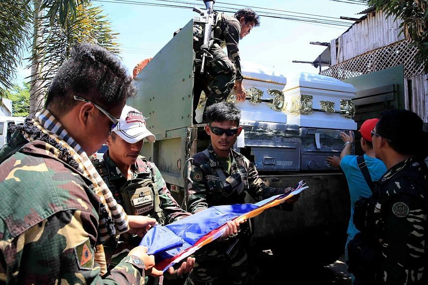 Government troops folding a Philippine flag beside the coffins of soldiers killed in the battle for Marawi, in the city of Iligan yesterday. Relief goods being prepared at a Manila mosque for delivery to Marawi last Saturday. Clashes in the southern