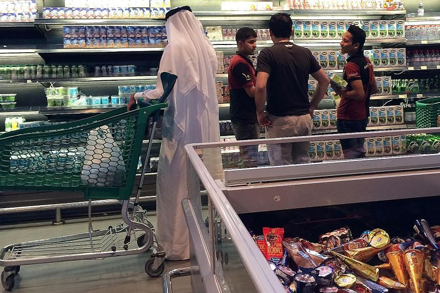 Customers at the al-Meera market in the Qatari capital Doha on Saturday. The blockade has disrupted food and material supplies to import- dependent Qatar. Iran yesterday said it had sent four cargo planes of food to Qatar and plans to provide 100 ton