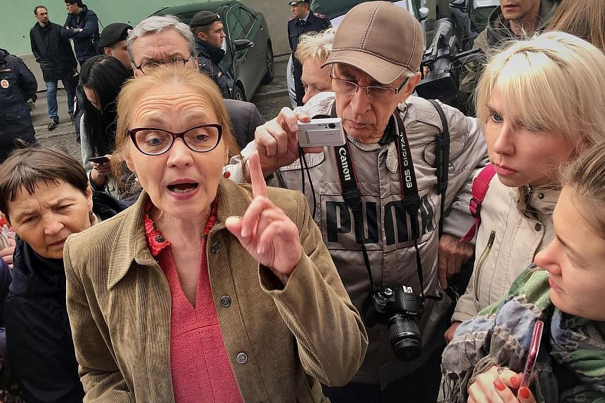 """Moscow city legislator Yelena Shuvalova addressing residents protesting against the demolition plan, including Ms Kari Guggenberger (second from right in picture). """"They forgot about us, the middle class,"""" said Ms Guggenberger, who bought her apartme"""
