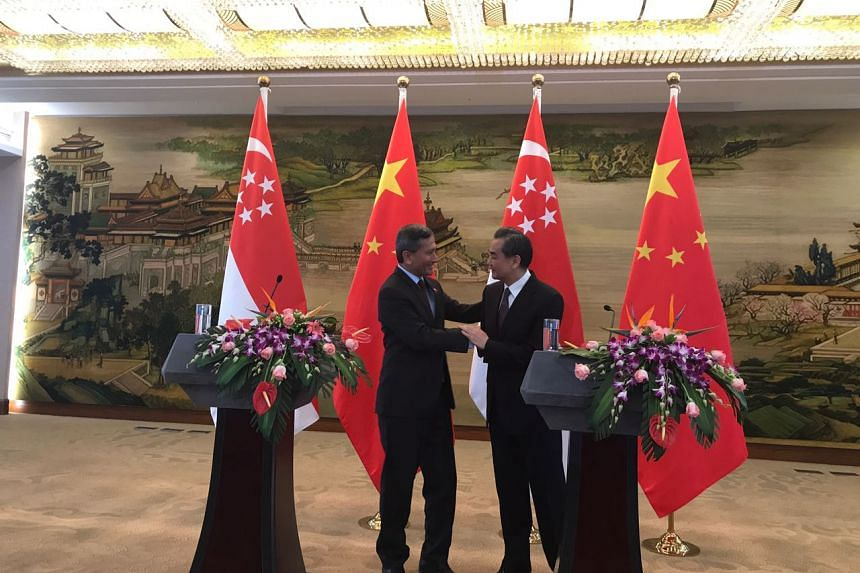 Singapore's Minister for Foreign Affairs Vivian Balakrishnan shaking hands with his Chinese counterpart Wang Yi.