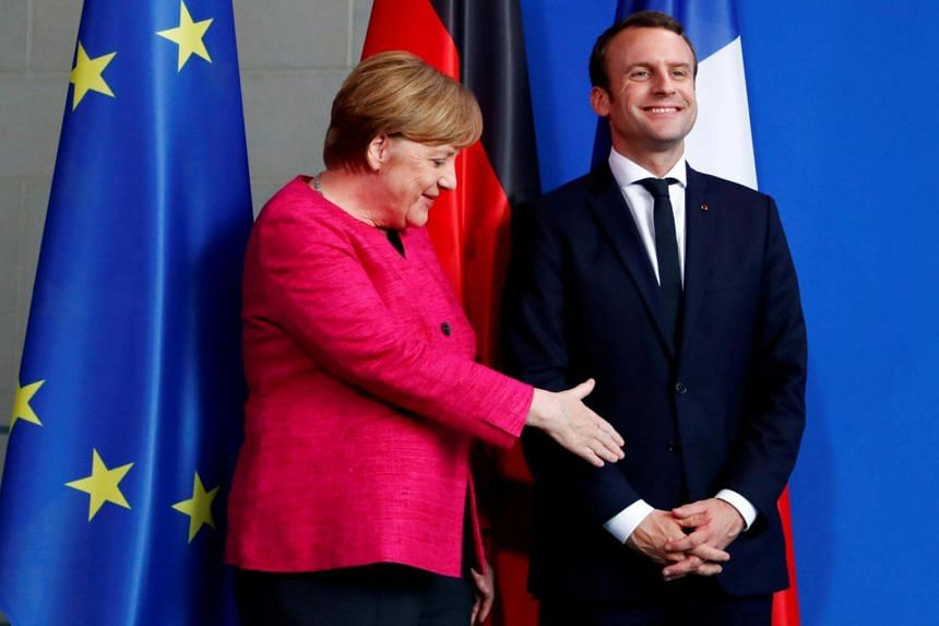 German Chancellor Angela Merkel offers a hand to French President Emmanuel Macron after a news conference in Berlin on May 15, 2017.