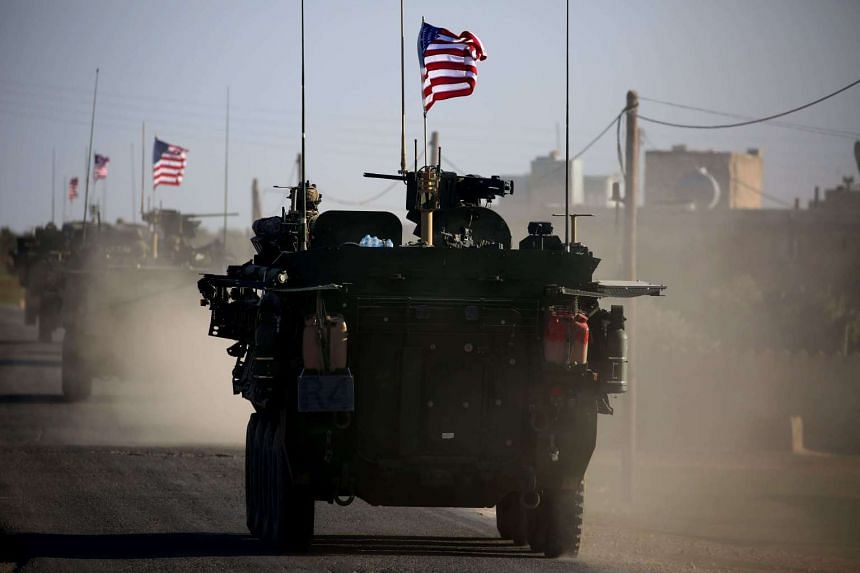 A convoy of US forces armoured vehicles drives near the village of Yalanli, Syria.