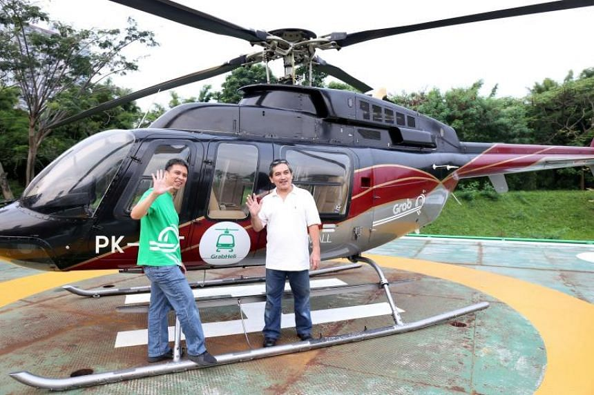 Ridzki Kramadibrata (L), managing director of Grab Indonesia, posing with a customer (R) prior to taking a helicopter taxi by Grab Indonesia in Jakarta.